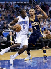 Orlando Magic's Victor Oladipo (5) drives around Indiana Pacers' George Hill (3) during the first half of an NBA basketball game, Wednesday, Jan. 6, 2016, in Orlando, Fla. (AP Photo/John Raoux)