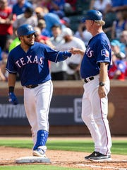 Texas Rangers' Jose Trevino, left, celebrates with first base coach Steve Buechele after collecting a single during the seventh inning of a baseball game against the Colorado Rockies, Saturday, June 16, 2018, in Arlington, Texas. (AP Photo/Sam Hodde)