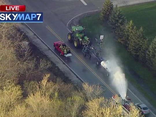 In this still image provided by ABC7 Chicago, a fire engine sprays water on a container of the chemical that farmers use for soil after after anhydrous ammonia leaked Thursday, April 25, 2019, in Beach Park, Ill. Authorities say dozens of people have been taken to hospitals.
