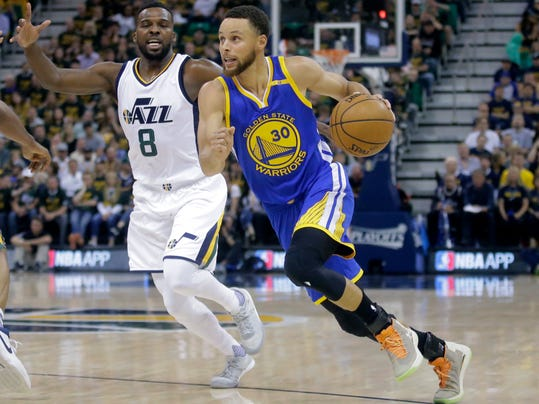 FILE - In this May 8, 2017 file photo, Golden State Warriors guard Stephen Curry (30) drives as Utah Jazz guard Shelvin Mack (8) defends in the first half during Game 4 of the NBA basketball second-round playoff series, in Salt Lake City. Point guards are cashing in so far in NBA free agency, teams have already paid nearly a half-billion dollars in commitments to five and Day 1 is still a long way from complete. Curry is among the early cashers-in and got $201 million from Golden State. (AP Photo/Rick Bowmer, File)
