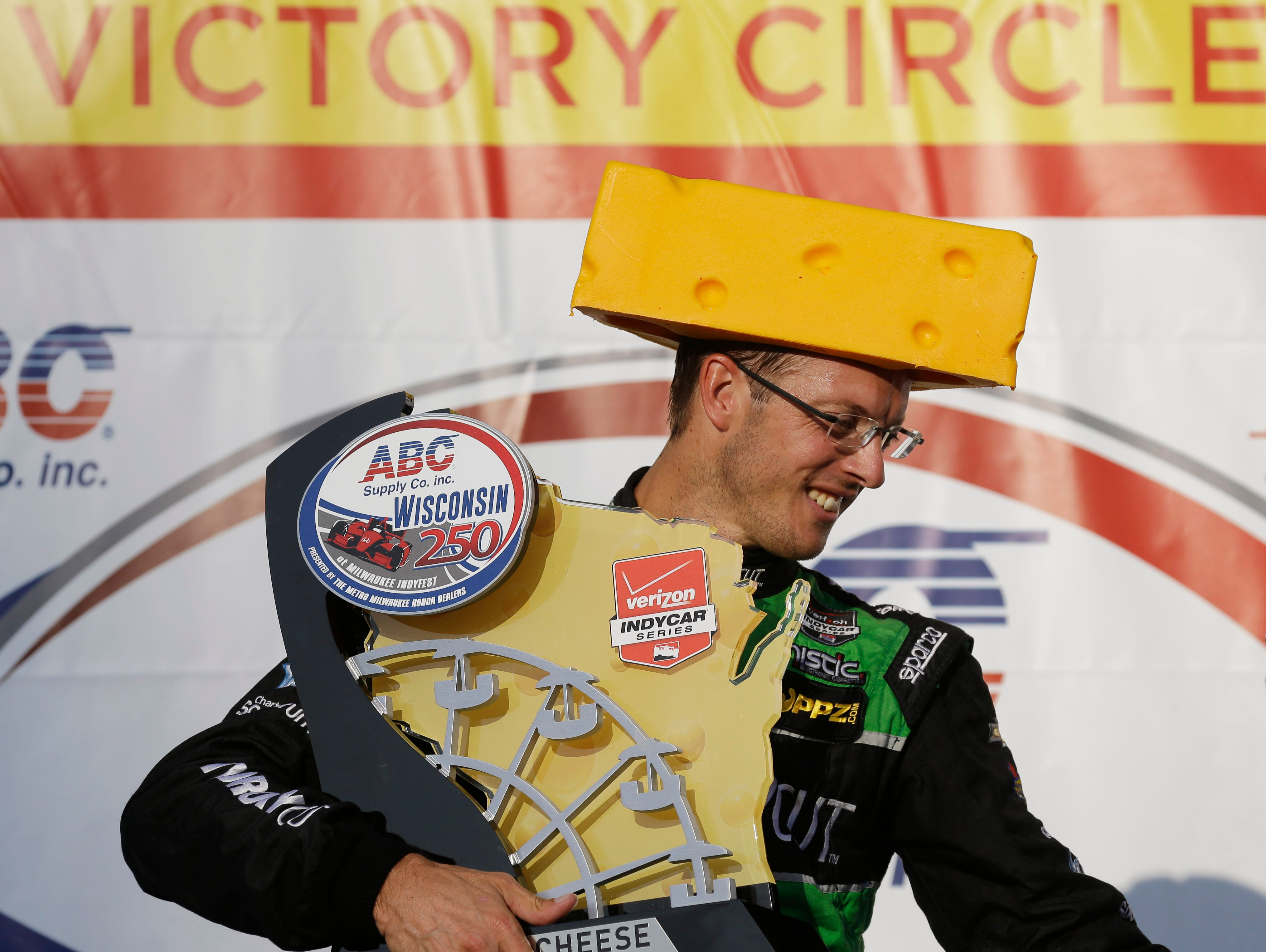 Sebastian Bourdais ,. of France, wears a cheese head hat and gets the winners trophy after the IndyCar Series race at the Milwaukee Mile in West Allis, Wis., Sunday, July 12, 2015.