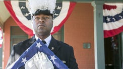 Keith Cooper holds a U.S. flag honors our veterans