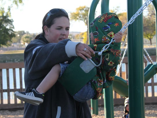 A mother helps her son on the swings at Project Playground