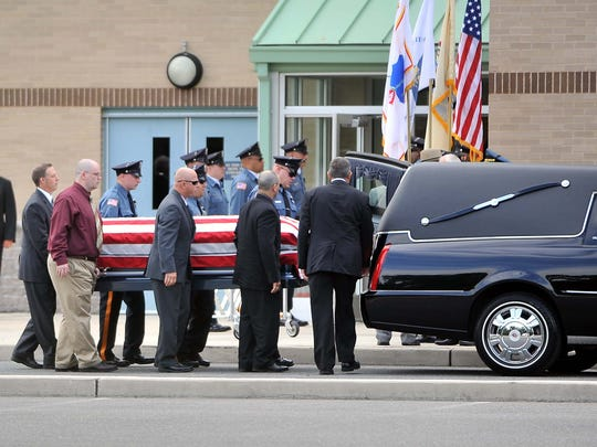 Pallbearers and officers carry the casket of Millville officer Christopher Reeves into Lakeside Middle School in New Jersey on  July 13, 2012.