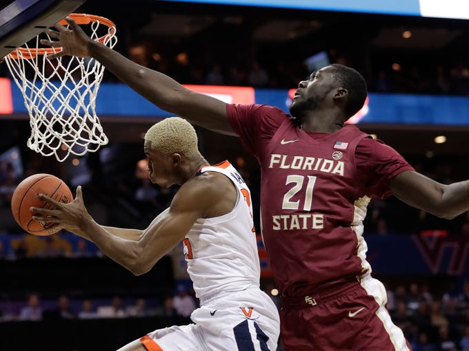 Virginia's Mamadi Diakite, left, drives past Florida State's Christ Koumadje, right, during the first half of an NCAA college basketball game in the Atlantic Coast Conference tournament in Charlotte, N.C., Friday, March 15, 2019. (AP Photo/Chuck Burton)