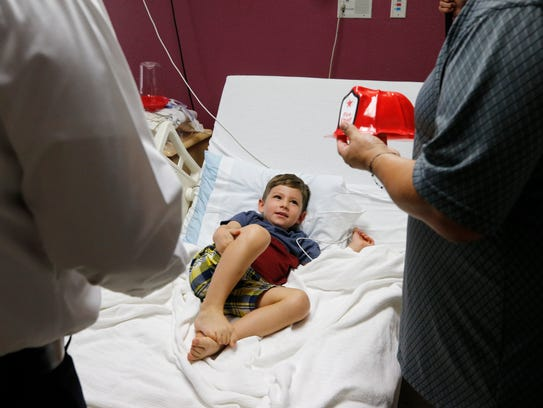 Collin Crawford 3, is all smiles after area firefighters surprised him with a small firefighter helmet and made him an honorary firefighter during the Hearts of Courage event at Providence Children's Hospital on Monday.