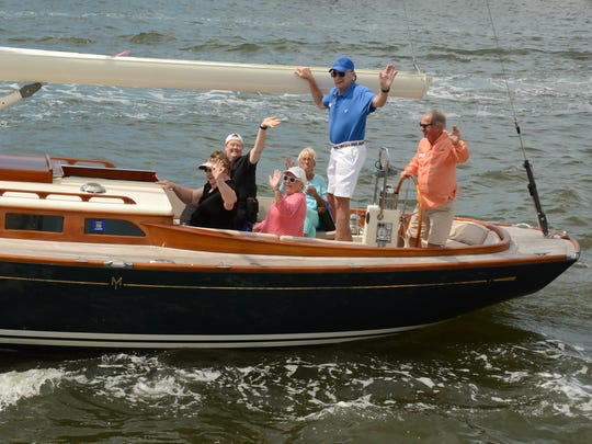 VIPs wave as they head out of Naples Bay for the Sailing Heals event.