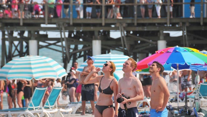 People on the beach north of the Cocoa Beach Pier watch the May 11 launch of the newest SpaceX  rocket, the Falcon 9 Block 5, launched from Kennedy Space Center's Pad 39A with the Bangabandhu-1 communications satellite.