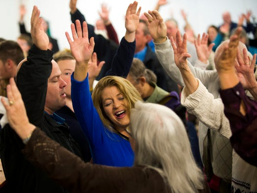Roaring Fork Baptist Church congregants raise their