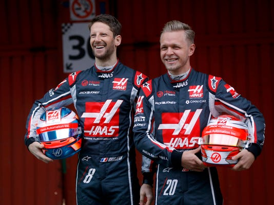 Haas drivers Romain Grosjean of France, left, and Kevin Magnussen of Denmark hold their helmets while posing for photos during the Haas team official presentation at the Catalunya racetrack in Montmelo, outside Barcelona, Spain, Monday, Feb. 26, 2018. (AP Photo/Francisco Seco)