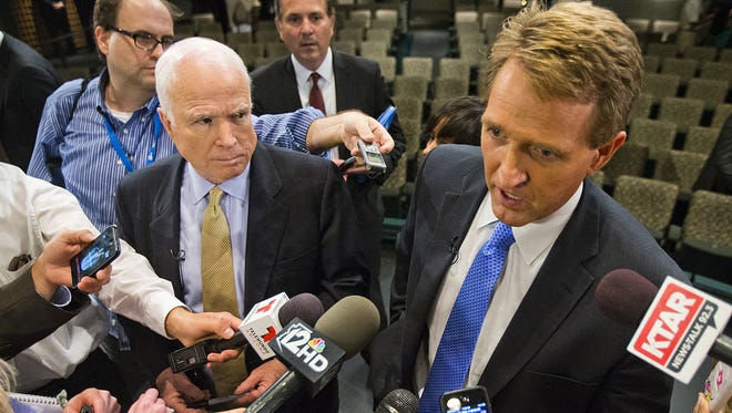 Sens. John McCain (left) and Jeff Flake answer questions at an immigration-reform forum in 2013 in Mesa.