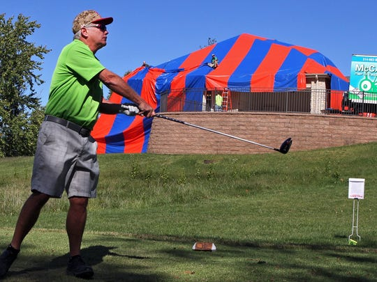 In this photo taken on Sunday, Oct. 5, 2014, Mike Wente tees off on the fourth hole at Whitmoor Country  Club in Dardenne Prairie, Mo., as a work crew, rear, from McCarthy Pest Control, finishes covering a house in preparation for fumigating the home to get rid of brown recluse spiders.