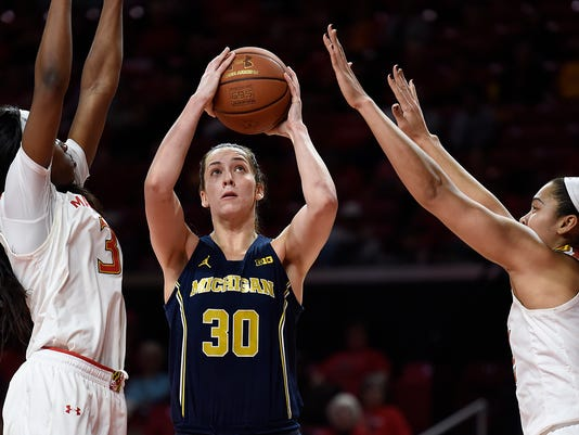 Michigan's Hallie Thome, center, shoots between Maryland's Kaila Charles, left, and Brionna Jones during the second half of an NCAA college basketball game, Thursday, Jan. 19, 2017, in College Park, Md. Maryland won 83-70. (AP Photo/Gail Burton)