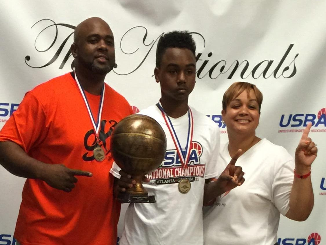 Rickie Wedlow, center, poses with his parents, Rick, left, and Tawanda after Wedlow's AAU team won the USBA seventh grade National Championship in Atlanta, Georgia, earlier this month.