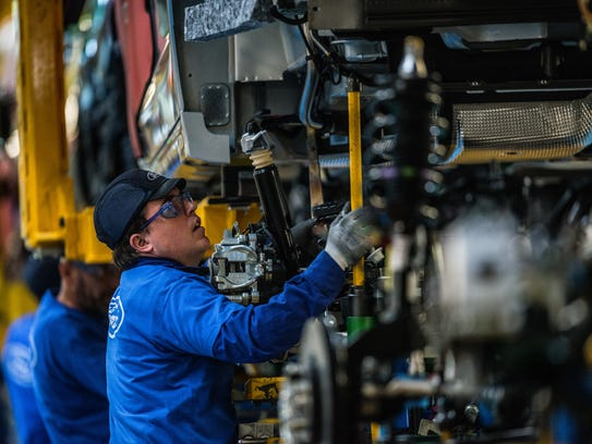 Employees work on Ford Mondeo vehicles on the production