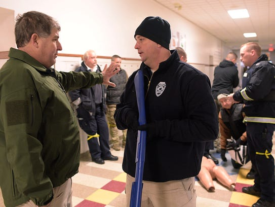 """Farmington Hills Fire Department EMS coordinator Jim Etzin (left), here talking with Farmington Police Sgt. Shane Walsh during an active-shooter training program, said fixing the school shooting epidemic is going to take an """"all hands on deck"""" approach."""