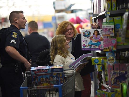Westland police Sgt. Robert Wilkie helps Karby Chouinard,