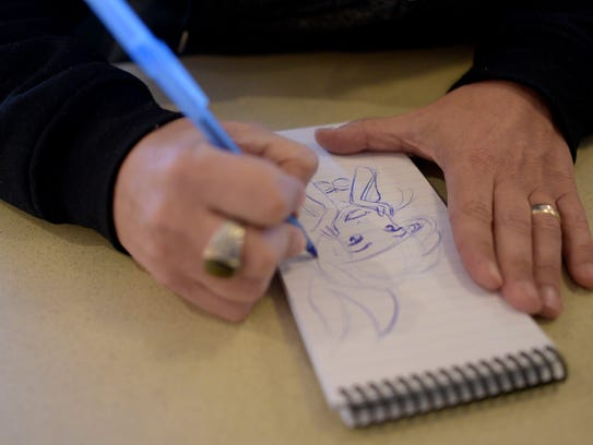 Keith Sintay makes a drawing during the interview.