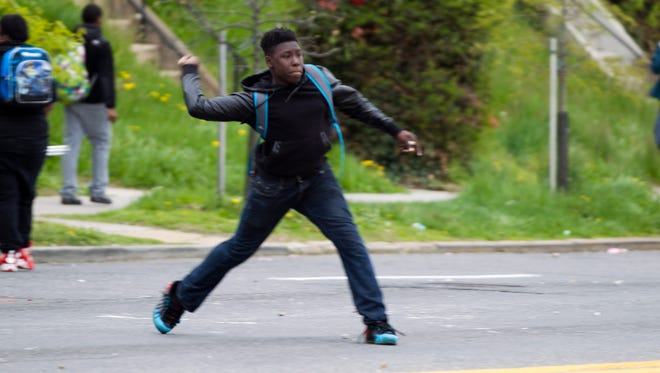 A demonstrator throws a rock at police after the funeral of Freddie Gray on Monday, April 27, 2015, in Baltimore.