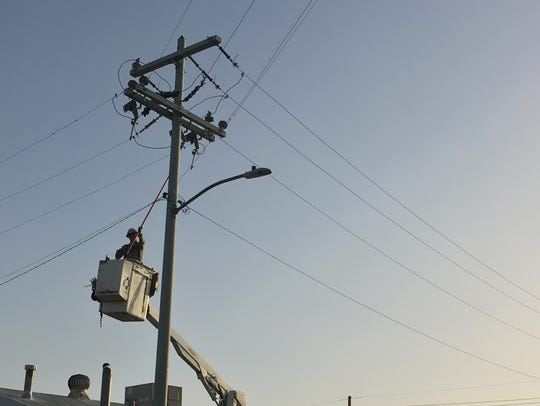 Repair crews worked on downed power lines in Phoenix.
