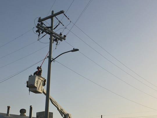 Repair crews worked on downed power lines in Phoenix.