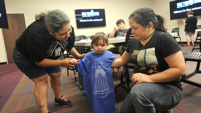 Anica Wolf, center, gets outfitted in a Doctor Who shirt, by mom Maria Lena, right, and Grandma Amparo Curiel, left, at a Doctor Who event at the south branch of the Abilene Public Library during Lib-Con.