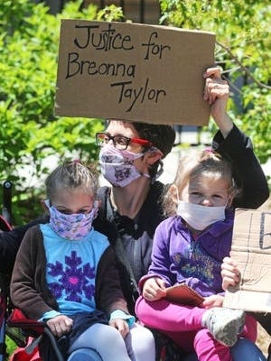 """Anne Schmidt of Milwaukee is joined by her twin daughters, Anya, left, and Naomi, 4, at the """"Sit-in for Change"""" protest on Saturday."""