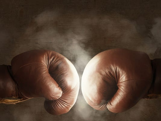 Two old brown boxing gloves hit together