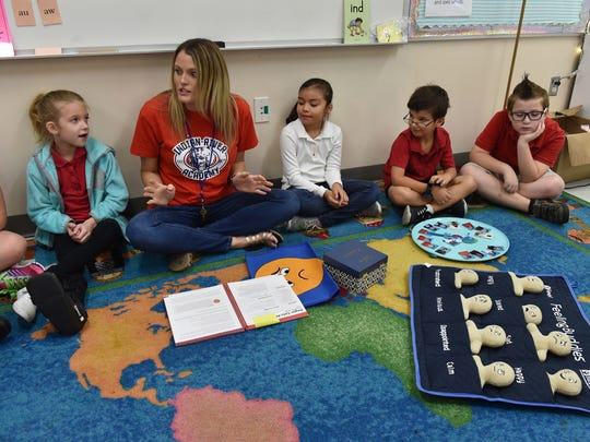 "Second-grade teacher Courtney Antosh (second from left) talks to her class about feelings as students (from left) Brooklyn Jared, Cristina Martinez, Timothy Powell, and Rhys Tredor listen in on Tuesday, Nov. 14, at Indian River Academy in Vero Beach. The class uses tools such as feeling buddies (front right), wish well board (circular plate), safe keeper box and the big feelings cape to keep track of their moods. The safe keeper box contains photos of all the students in class for the day, the wish well board is used to keep track of students not feeling well, the feeling buddies and feelings cape are used to show emotions. ""It helps the kids to be successful,"" Antosh said."