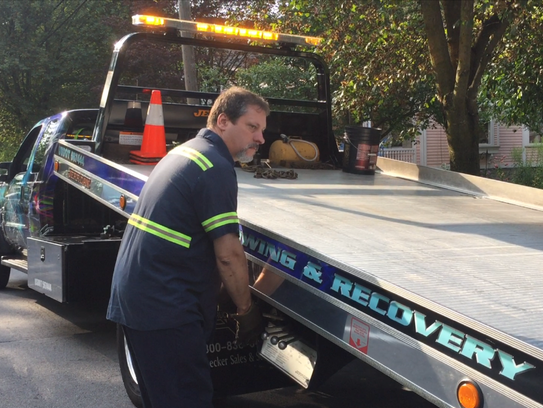 Tow truck driver John McDonald prepares to load a vehicle