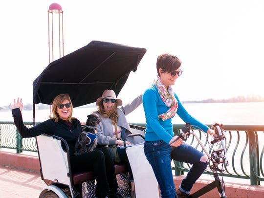Mary Allen, owner of Evansville Pedicab, gives a ride to friends AJ White and Michelle Crowley along Evansville's riverfront. She was testing out the pedicab Sunday after receiving it Saturday night.