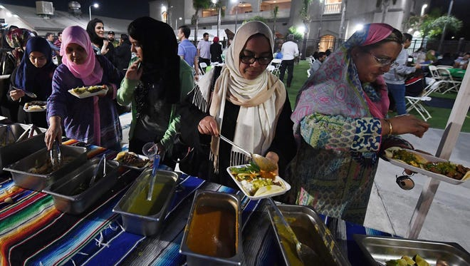 """Muslims break their Ramadan fast after sunset by eating halal Mexican tacos from a food truck, during a campaign called """"Taco Trucks at Every Mosque"""" at the Islamic Center in Santa Ana, Calif., on June 14, 2017."""