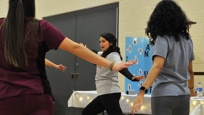 Midwestern State University nursing student Kathy Lim teaches a short yoga class Friday afternoon during MSU's annual Community Health Care Fair held in the D.L Ligon collisuem.