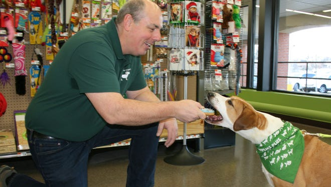 Pet Supplies Plus owner, Wade Deffenbaugh of the Basking Ridge section of Bernards, treats his rescue dog, Bonnie, to an all-natural, made-in-the-USA gourmet donut at the new Pet Supplies Plus in Chester.