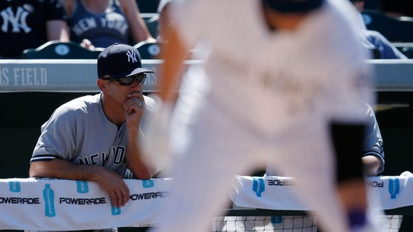 New York Yankees manager Joe Girardi, back, looks on as Colorado Rockies' Mark Reynolds steps back up to the plate to bat after dropping out of the way of an inside pitch thrown by New York Yankees relief pitcher Dellin Betances in the seventh inning of a baseball game Wednesday, June 15, 2016, in Denver. Colorado won 6-3.