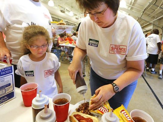Rachel Swicord, 6, watches as her mother, Amy Swicord, puts sauce on her barbecue at the Blackman Barbecue at Lane Agri-Park in Murfreesboro in 2014. The 67th annual Blackman Barbecue is Friday.