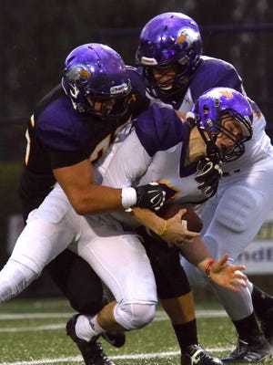 Gold quarterback David Murray is tag-teamed by the Purple's Kyler Lacy (left) and Zavier Buzzard duiring Ashland University's spring football game Thursday night.