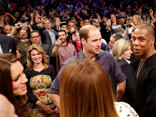 Britain's Prince William (second from right) talks with rapper and entrepreneur Jay Z (far right) as their wives, Kate, Duchess of Cambridge (left) and Beyoncé (foreground center) chat during the Cleveland Cavaliers-Brooklyn Nets game Monday, Dec. 8, 2014, at the Barclays Center in New York.