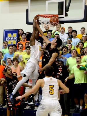Moeller guard Trey McBride dunks on Wilmington forward Chris Woolery for the final points of the game. Moeller defeated Wilmington, 40-31.