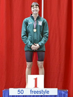 Ashley Volpenheim from Mason stands atop the winner's platform of the 50 yard Freestyle at the Southwest District Swimming Championships at Miami University.