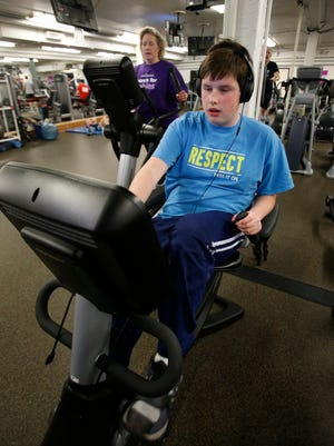 Joan Kelley works out with her son, Ian, at the Brandywine YMCA Tuesday.
