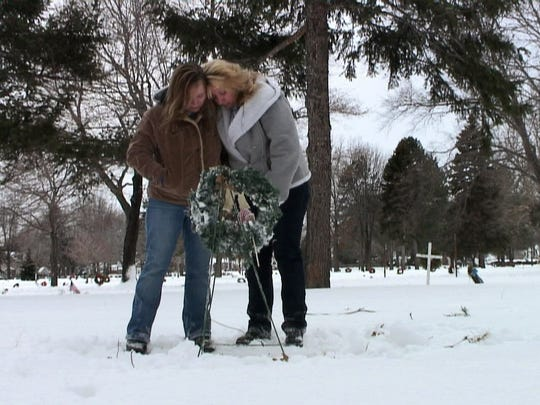 Rita DeCann and Michelle Walkowicz at the grave of their sister Wanda Walkowicz.  The two visit Wanda regularly at Holy Sepulchre Cemetery. Wanda is one of three young girls killed in the early 1970s.
