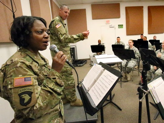 """Vocalist Sgt. 1st Class Linda Wolfe sings out """"Go Tell it on the Mountain"""" as Capt. Richard Winkels, background, leads the band during a rehearsal for the 1st Armored Division Band at Fort Bliss. The band will perform a concert Dec. 17 at the Plaza Theatre."""