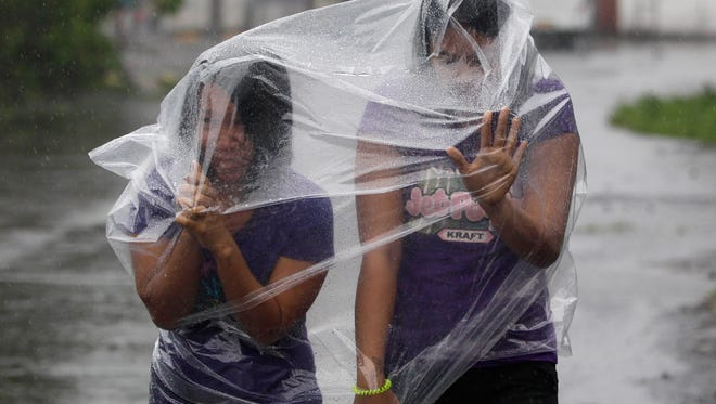 In this Sunday, Dec. 7, 2014 photo, Filipino residents use plastic sheets to protect them from rains and strong winds brought by Typhoon Hagupit in Legazpi, Albay province, eastern Philippines. Typhoon Hagupit slammed into the central Philippines' east coast late Saturday, knocking out power and toppling trees in a region where 650,000 people have fled to safety, still haunted by the massive death and destruction wrought by a monster storm last year. (AP Photo/Aaron Favila)