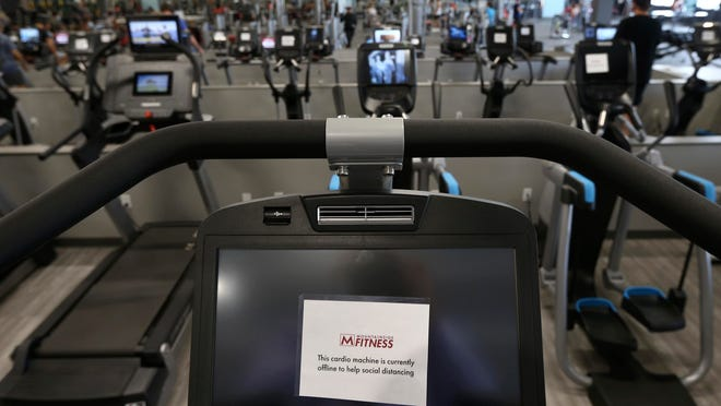Some gym equipment machines are turned off so clients can physically distance at Mountainside Fitness in Phoenix.