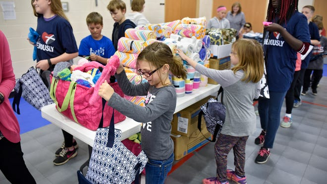 Prince of Peace Lutheran School students pack items into 150 reusable bags Monday, May 22, in the school's gymnasium. The bags will be distributed to local cancer patients undergoing chemotherapy.