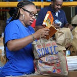 LaToya Carr helps sort food items as part of a group of volunteers from J.P. Morgan Chase. The food items were recently donated to the Food Bank of Northeast Louisiana.