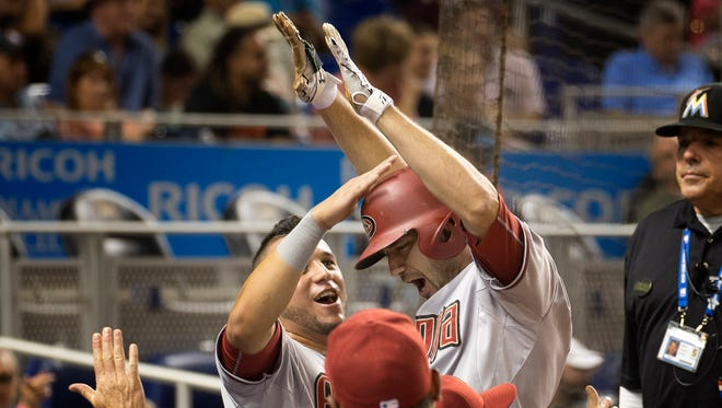 Arizona Diamondbacks'  David Peralta, left, celebrates with A.J. Pollock during the eighth inning of a baseball game against the Miami Marlins in Miami, Tuesday, May 19, 2015, after Pollock hit a go-ahead two-run home run. The Diamondbacks won 4-2.