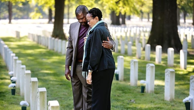 Fort Pillow decendants Norris Thomas (left) and Tara Saunders bow their heads in remembrance during a ceremony at the Memphis National Cemetery to honor the African American Union troops slaughtered by Confederates on April 12, 1864 after the garrison at Fort Pillow surrendered. The graves of over 100 of the victims were recently found at the local veterans cemetery.