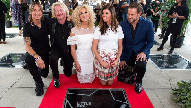 Keith Urban, left, joins Little Big Town as they view their star during the Music City Walk of Fame Induction ceremony at the Country Music Hall of Fame Sept. 14, 2017.